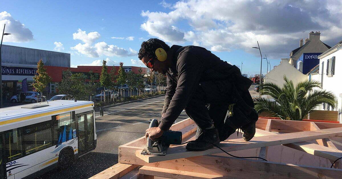 ismael charpentier travaille sur les toits avec son pantalon de travail