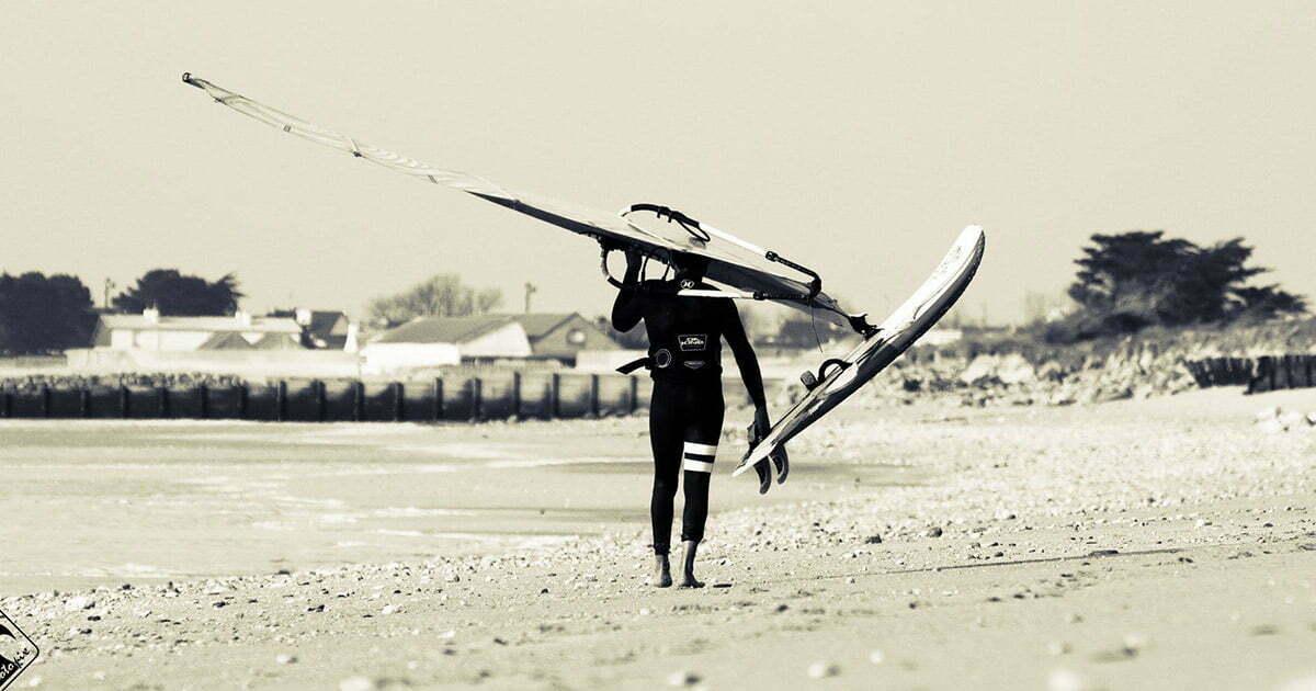 ismael porte sa planche à voile sur les plages bretonnes
